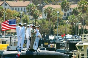 Officers stand on the sail of the Los Angeles-class attack submarine USS Albuquerque (SSN 706) as she arrives at her new homeport at San Diego, Calif.